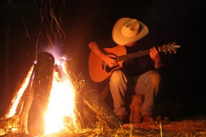 texan cowboy playing guitar in front of campfire
